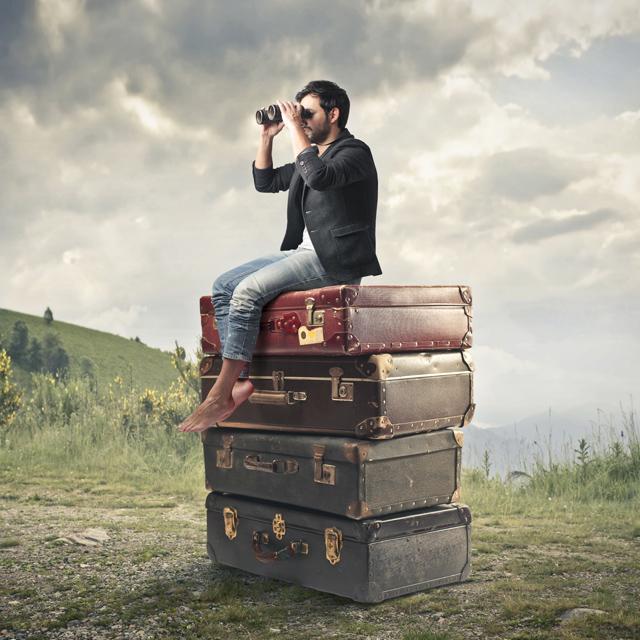 Mann sitzt auf Kofferstapel und schaut suchend durchs Fernglas