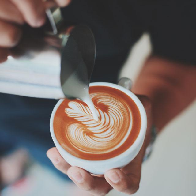 Barrista gibt Milch in Kaffee