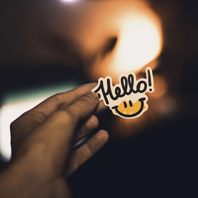 Hand die Icon mit Aufschrift Hello hält